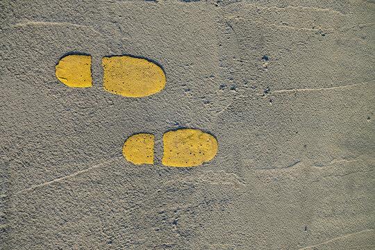 Two yellow shoeprints on concrete pavement.