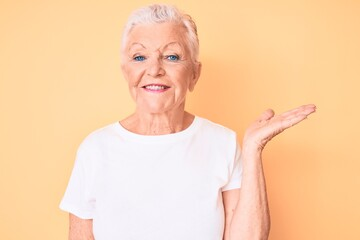Senior beautiful woman with blue eyes and grey hair wearing classic white tshirt over yellow background smiling cheerful presenting and pointing with palm of hand looking at the camera. Wall mural