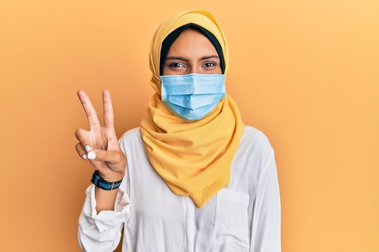 Young brunette arab woman wearing traditional islamic hijab and medical mask smiling with happy face winking at the camera doing victory sign. number two.