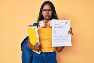 Young indian girl wearing backpack showing a passed exam depressed and worry for distress, crying...