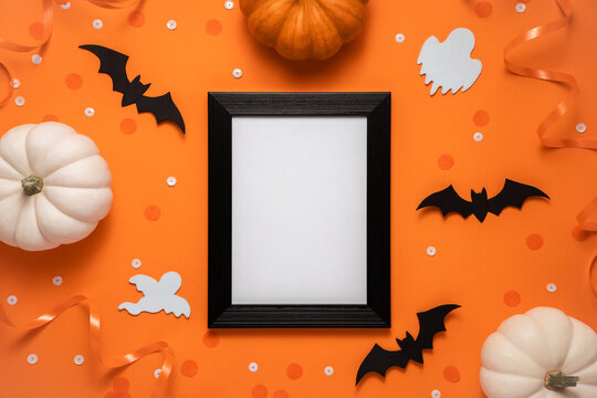 Creative halloween flat lay composition: black frame, bats, pumpkins, confetti and ghost on orange background with place for text, top view.