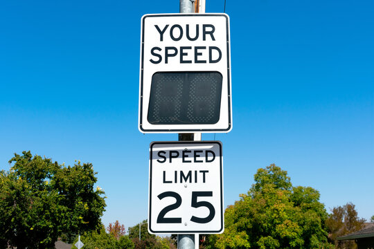 Your Speed, a radar speed sign that displays vehicle speed as motorists approach. 25 mph speed limit sign in residential neighborhood