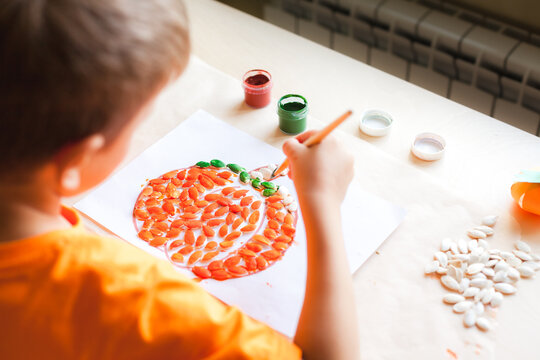 Making pumpkin from seeds on white paper, Halloween DIY concept. Step by step instruction Step 4 Paint the seeds with green color