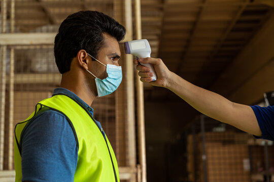 Young Indian factory warehouse worker wearing face mask getting body temperature check with infrared thermometer scanner before working. Security measure at workplace in Coronavirus Covid 19 pandemic