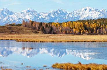 Yellowed forest and snow-capped mountain peaks are reflected in a calm river covered with a crust of ice on a sunny autumn day. Beautiful landscape, natural background, autumn travel