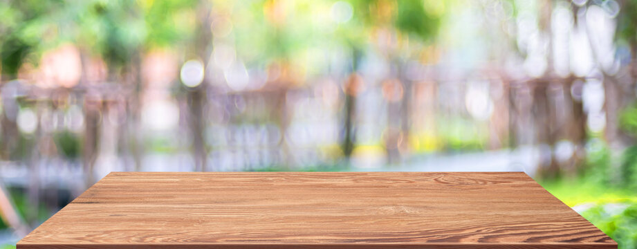 spring background.Empty brown wooden table with blur tropical  tree in garden boekh background,banner mockup template for display of product