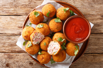 Hot fried sauerkraut balls with ham and cheese close-up in a plate on the table. horizontal top view from above