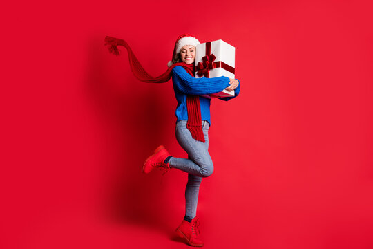 Photo portrait full body cheerful woman hugging present box smiling closed eyes standing on one leg scarf flowing isolated on bright red colored background