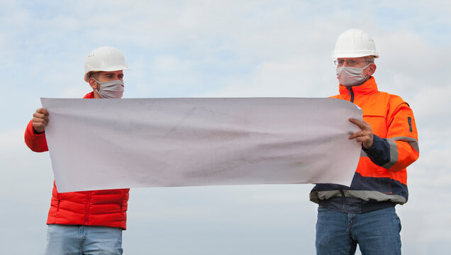 Young and mature engineers or workers discussing a construction plan with face mask and social distancing