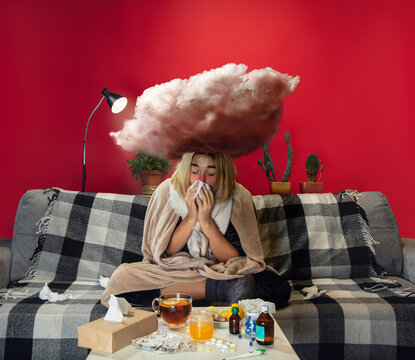 Ill young girl with fever and cold looks suffering. Feeling sick, blue, snuffling. Big cloud above the head like weight during feeling ill. Cold, virus, seasonal grippe. Woman sitting on sofa at home.