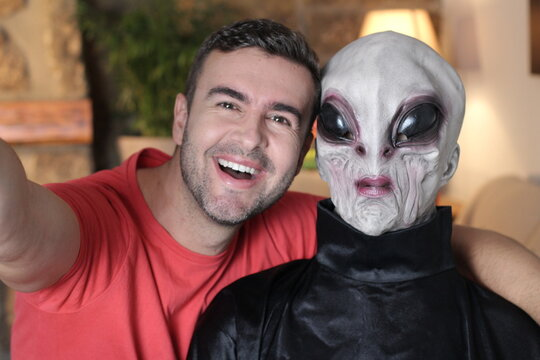 Excited man taking a selfie with an alien