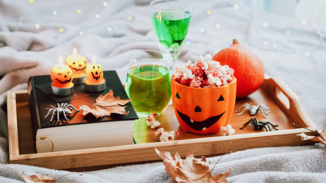 Book, halloween decor, candles, popcorn and drinks on tray on bed, halloween reading concept with bokeh background. Still life for Halloween at home