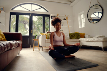 Young healthy beautiful woman in sportive top and leggings practicing yoga at home sitting in lotus pose on yoga mat meditating smiling relaxed with closed eyes