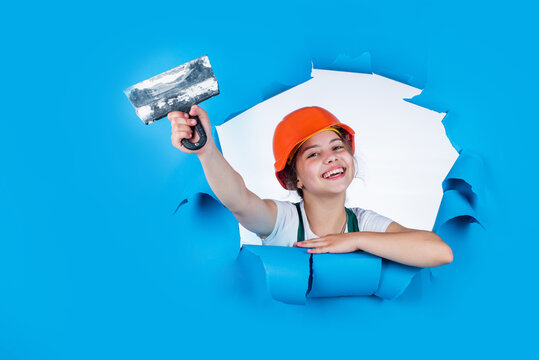 builder in coveralls and helmet with spatula. kid repair wall with spackling paste. Home renovation. Kid with tool. happy small construction girl with spatula. teen girl use putty knife