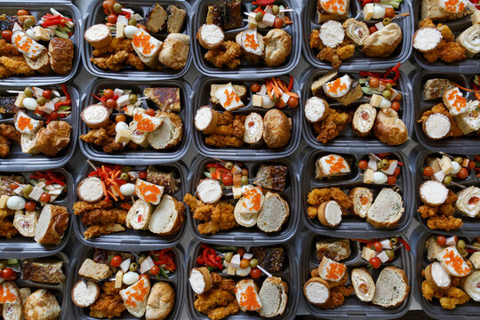 Catering. Business lunch. Dispensing food into plastic boxes. Social assistance. Lunch at a business seminar. Food for to the homeless on holidays.