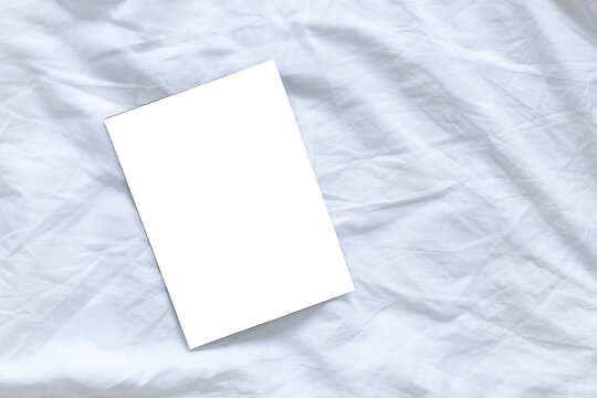 Blank flyer poster mocap on white sheet bed background with copyspace, top view, flat lay