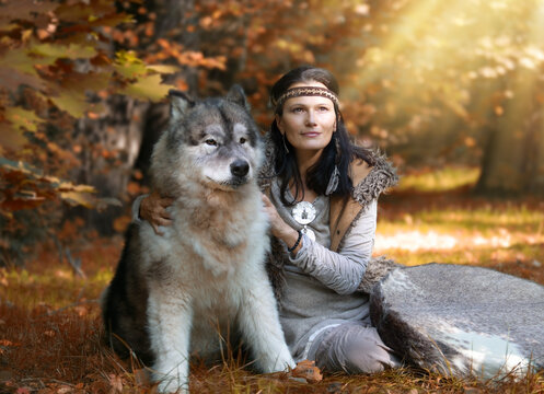 Portrait of a Shaman woman with an Alaskan Malamute dog in the forest