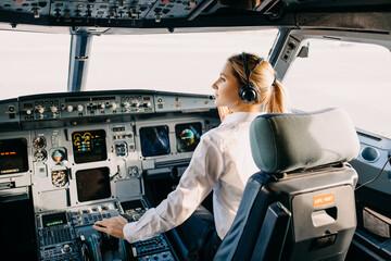 Fototapeta Woman pilot sitting in airplane cockpit, wearing headset. obraz