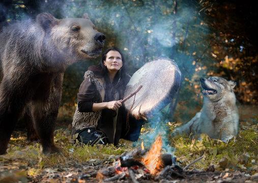 Shaman woman plays a tambourine among wild animals