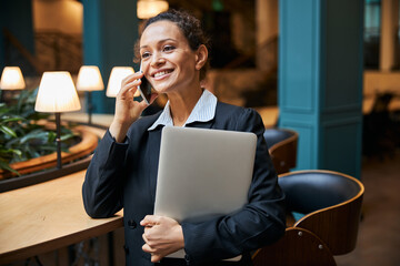 Delighted young office worker talking per telephone