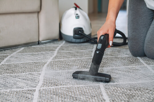 Woman cleaning carpet with a steam cleaner
