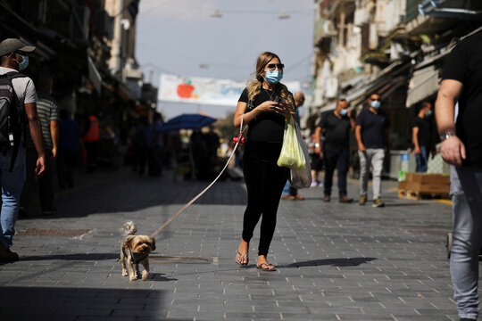 A woman wearing a protective face mask walks with a dog at a market amid Israel's second-wave coronavirus disease (COVID-19) lockdown, in Jerusalem