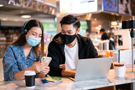 Asian couple take off mask protection uses their laptop computer and smartphone to relax during a flight in lounge at international airport.Young man and woman laugh smile together in coffee shop cafe