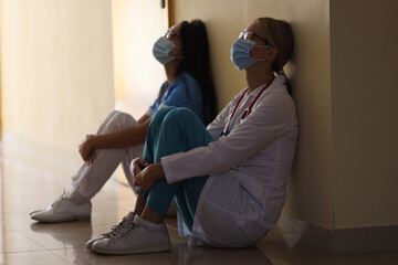 Young female doctor and nurse in medical masks sit in corridor of hospital. Emotional burnout of...