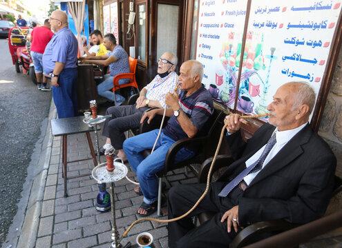 Men smoke hookah in Sidon