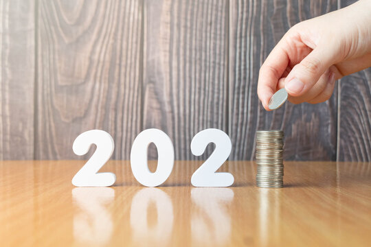 2021 New year saving money and financial planning concept. Hand putting coins on stack with 2021 number on wooden table. Creative idea for business growth, tax payment, investment and banking.