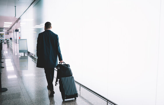 Back view of formally dressed male pilot walking near promotional backdrop with copy space area for travel or aviation advertising, businessman with luggage suitcase going to airport terminal