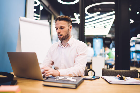 Caucasian male employee reading web information on browsed site survey during productive working process at office table, skilled businessman using 4g internet for making online banking and booking
