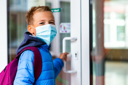 the boy wearing protective mask is trying to open the school door. Behind the backpack Schoolboy look at camera