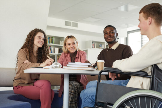 Low angle view at multi-ethnic group of students studying in college library featuring young man using wheelchair in foreground