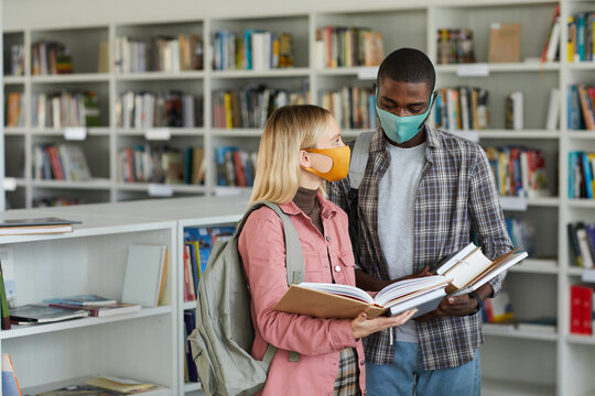 Waist up portrait of two students wearing masks while standing in school library and holding books, copy space