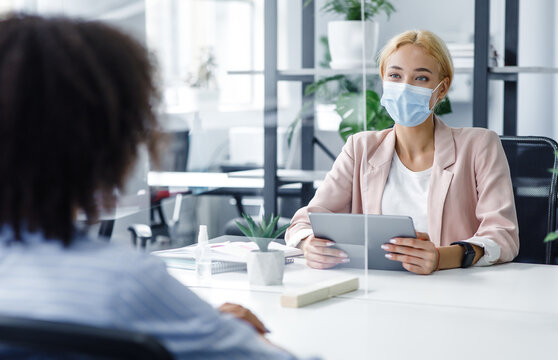New normal and modern interview during covid-19 outbreak. HR manager with laptop looks at african american woman through protective glass