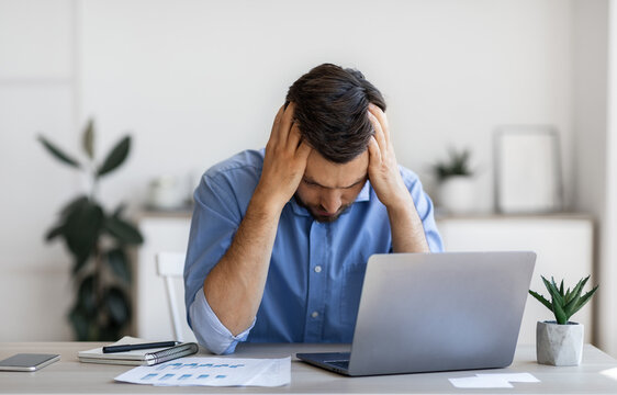Business Problems. Desperate Millennial Businessman Sitting At Workplace In Office, Touching Head