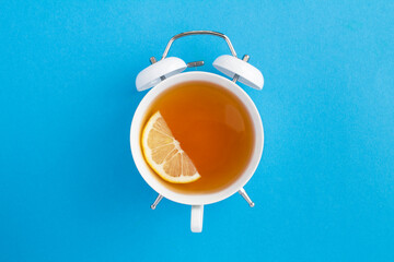 Top view of tea on the dial of the white alarm clock in the center of the blue background