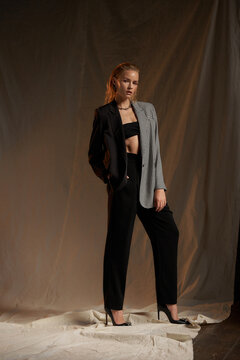 Full length fashion studio portrait. Elegant woman with make-up and wet blonde hair.Pretty slim female woman in bandeau top, trousers and blazer with chain necklace standing against textile background