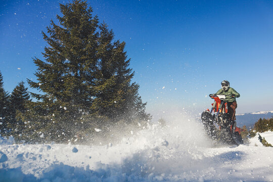 Snowbike rider in mountain valley in beautiful snow powder. Snowdirt bike with splashes and trail. Snowmobile winter sport riding
