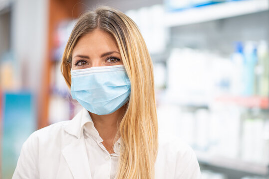 Smiling pharmacist wearing covid coronavirus mask in her pharmacy