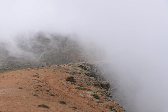 Smoke screen. Foggy path on the edge of a volcano. On a path in the mountains, white fog rises up the mountain. Part of the way can no longer be seen.