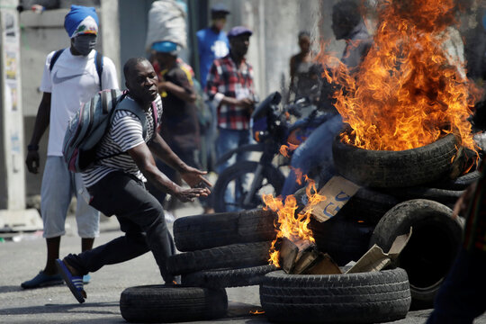 A man throws a tire into a burning barricade during a protest in the streets of Port-au-Prince