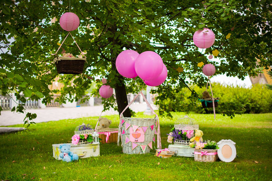 street decorations for a children's party. Wicker baskets with balloons in a green park