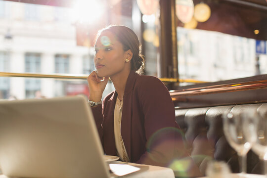 Serious businesswoman with laptop working in sunny restaurant