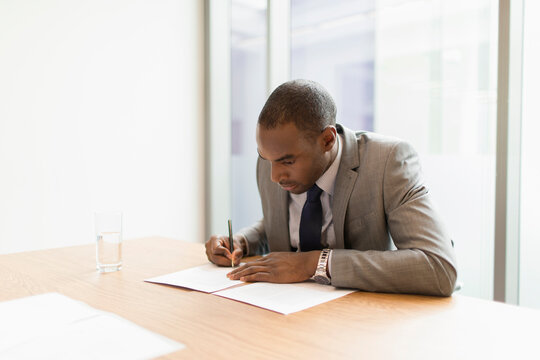 Businessman filling out paperwork in conference room
