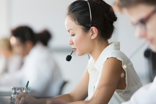 Focused businesswoman with headset in call center