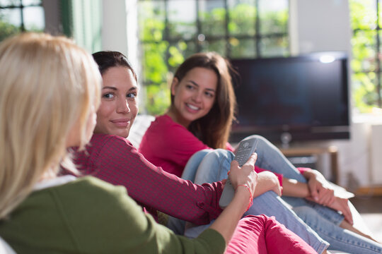 Young women friends watching TV on sofa