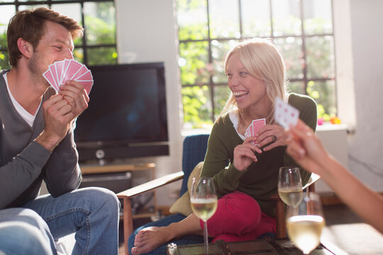 Happy friends playing cards and drinking wine