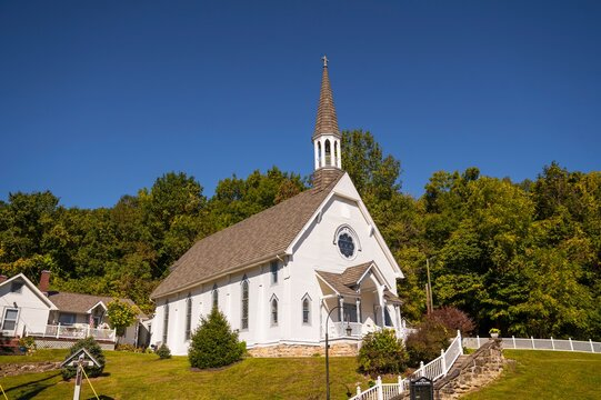 This image shows and idyllic rural, small town church chapel building with trees and a blue sky behind.